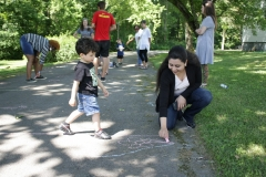 Mom and son making chalk drawing of spring flowers